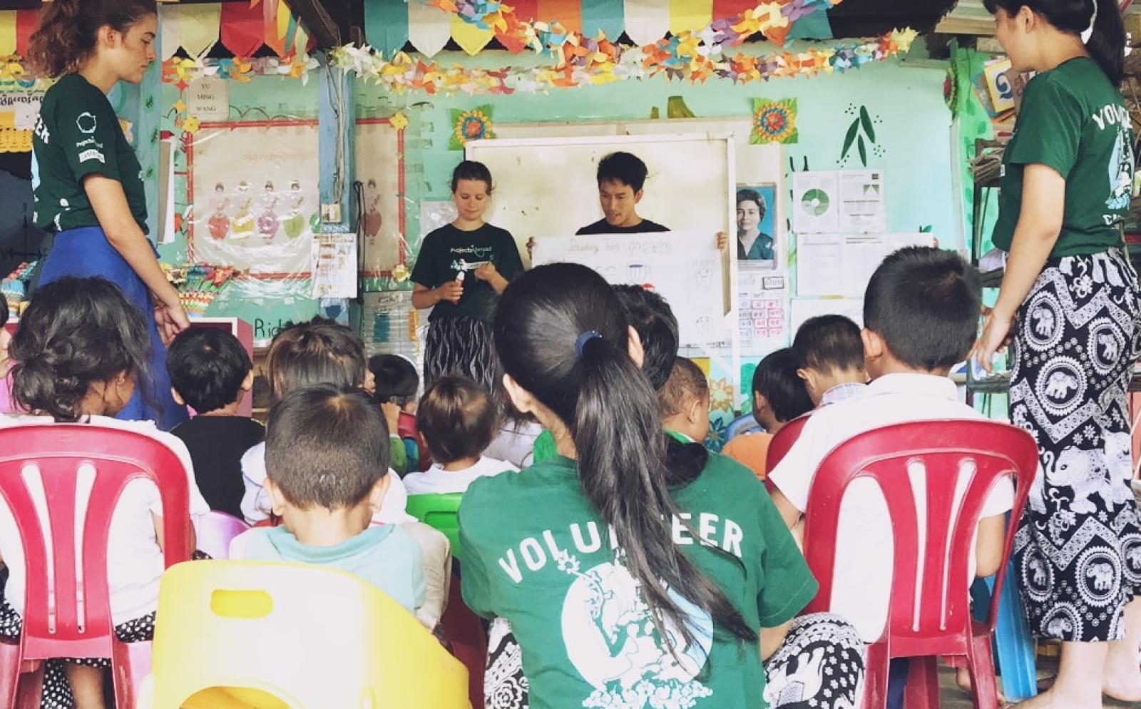 カンボジアの幼い子供たちに歯磨き指導を行う高校生ボランティアたち